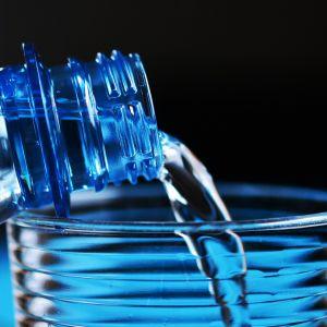 Vettä kaadetaan muovipullosta vesilasiin.