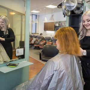 Parturi-kampaajaopiskelija Sanni Fagerlund harjaa asiakkaan hiuksia.