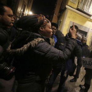 Afrikkalaisia maahanmuuttajia ja poliiseja Madridin kadulla.