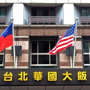 Kolme lippua liehuu talon seinustalla, tekstiä perinteisin merkein kirjoitettuna.