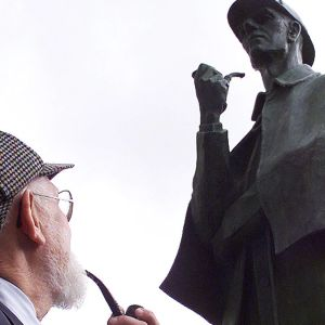New Yorkin Sherlock Holmes-seuran jäsen Jim Moran katselee Holmesia esittävää patsasta Lontoossa.
