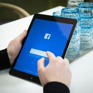 Mies kahvilassa kirjautumassa Facebookiin iPadilla.