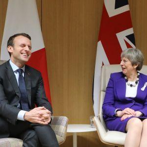 Pukumies naureskelee ja nainen jakku puvussa katsoo miestä huvittuneen.