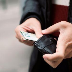 mies laittaa seteliä lompakkoon