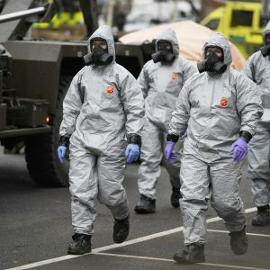 Neljä vaaleisiin kemiallisiin suojapukuihin pukeutunutta henkilöä kävelee kadulla.