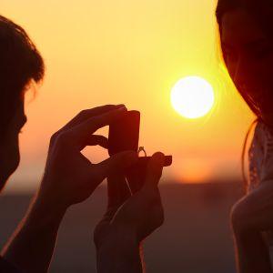 Mies tarjoaa naiselle sormusta kosinnan merkiksi.