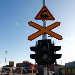 Etualalla junaradasta ja tasoristeyksestä varoittava liikennemerkki ja varoitusvalot. Taustalla näkyy kontteja.