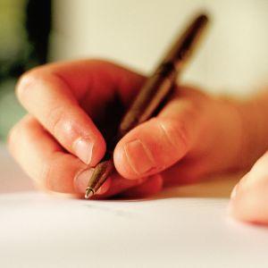 Lapsi kirjoittaa kynällä paperille.