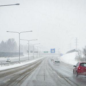 Autoja ajaa lumisateessa.
