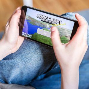 Nuori pelaa Minecraft -peliä puhelimellaan.