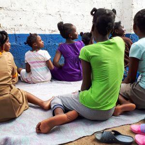 Orpokodin lapsia istuu sisäpihalla.