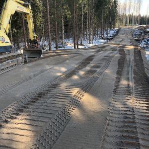 Kaivinkone tekemässä tienpohjaa