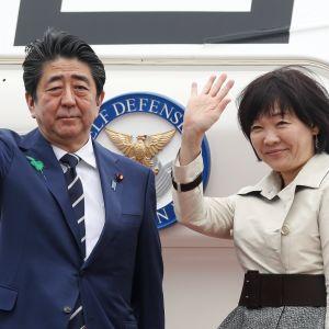 Kuvassa pääministeri ja hänen vaimonsa vilkuttavat ja hymyilevät ennen nousuaan koneeseen.