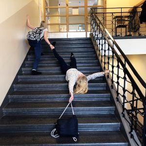 Kuvassa kaksi oppilasta koulun portaissa.