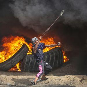 Palestiinalainen mielenosoittaja linkoaa kiveä, taustalla palavia autonrenkaita ja paksua savua.