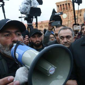 Armenian presidentti Armen Sarkisian (oik.) ja oppositiojohtaja Nikol Pashinyan (vas.) kuvattuna lehdistön ympäröimänä mielenilmauksessa Jerevanissa 21. huhtikuuta.