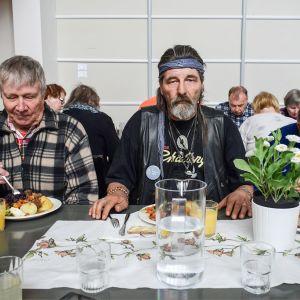 kolme miestä ruokapöydässä