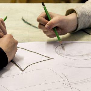 Koululaiset piirtävät lyijykynällä paperille