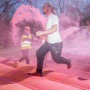 Ihmisiä juoksee väripilven läpi juoksutapahtumassa