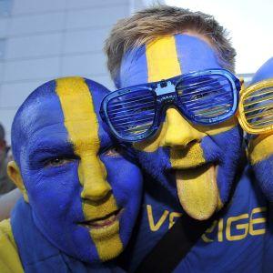 Kolme miestä, jotka ovat maalanneet kasvonsa Ruotsin lipun värein. Yksi näyttää keltaiseksi väritettyä kieltään.