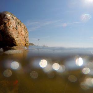 Lähikuva rantakivestä ja vedestä, jossa aurinko kimmeltää.