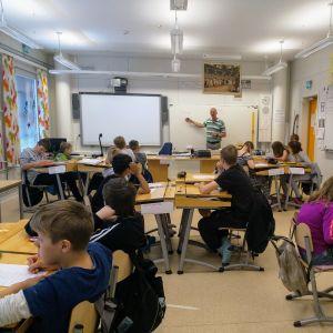 Opettaja ja oppilaat suomen kielen tunnilla.