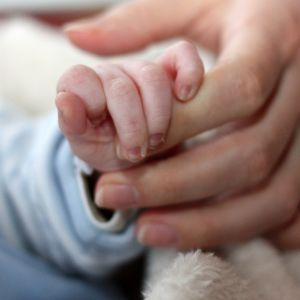 Käsi pitelee vauvan pientä kättä.