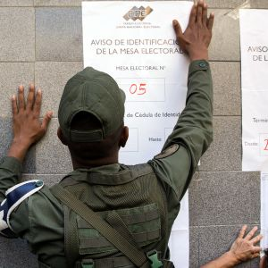 Poliisi kiinnittää seinään informaatiolappuja äänestämisestä.