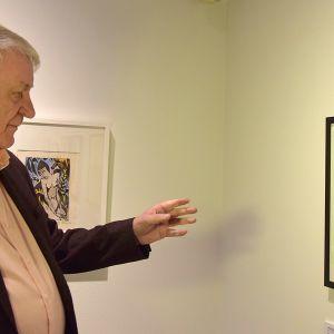 Mies katsoo ja osoittaa taideteosta seinällä