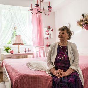 Lyyli Vassinen istumassa vaaleanpunaisen sävyisessä makuuhuoneessaan.