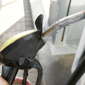 Mies tankkaa bensiiniä autoonsa .
