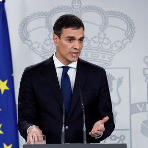 Espanjan pääministeri Pedro Sanchez puhuu, taustalla on Espanjan ja EU:n lippu.
