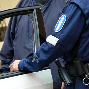 Poliisi poliisiauton ovella.