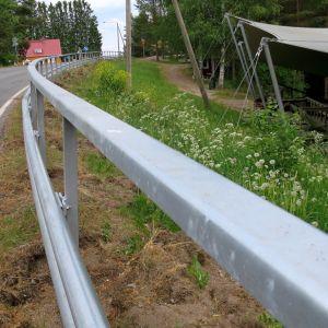 Korkea suojakaide erotta kesäteatterin ja maantien toisistaan