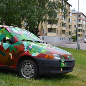 Etualalla maalattu auto vihreällä nurmella, taustalla tie Kotkan keskustassa, jolla liikkuu autoja.