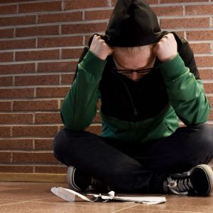 Nuori istuu lattialla kirje edessään
