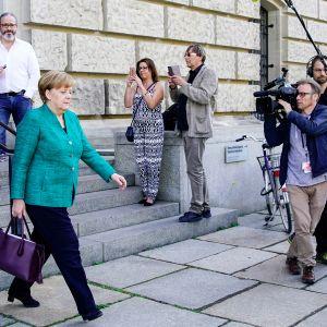 ihmiset kuvaavat ulos tulevaa Angela Merkeliä