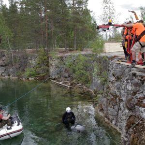 Tutkimusryhmä laskemassa sukellusrobottia louhokseen