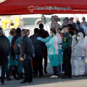 Pelastustyöntekijöitä ja siirtolaisia Valencian satamassa.