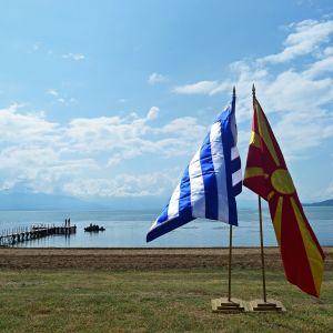 Kreikan ja Makedonian liput vierekkäin järven rannalla.
