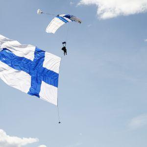 Laskuvarjohyppääjä tuo Suomen lipun avajaisissa Ilmavoimat 100 -vuotta juhlalentonäytöksessä Tikkakoskella.