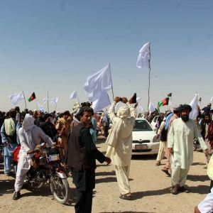 Talibanin taistelijoita saapumassa Afganistanin Kandahariin juhlimaan paatokauden päättymistä. Ihmisjoukko aukiolla käsissään valkeita lippuja ja Afganistanin lippuja.
