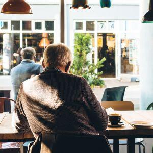 Iäkäs mies kahvilassa.