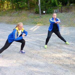 Kolme nuorta venyttelee ennen juoksua