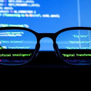 tietokoneen edessä silmälasit johon heijastuneena tekstiä
