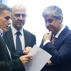 Kreikan valtiovarainministeri Euclid Tsakalotos esittelee kädessään olevia papereita EU:n talouskomissaari Pierre Moscovicille ja euroryhmän puheenjohtajalle, Portugalin valtiovarainministerille Mario Centenolle valtiovarainministerien kokouksessa Luxemburgissa.