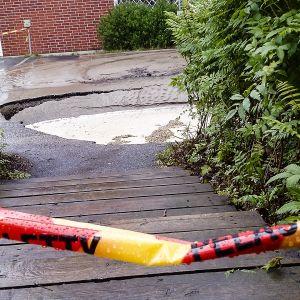 Maa on vajonnut ja asfaltti repeytynyt jyväskyläläisen kerrostalon pihalla.