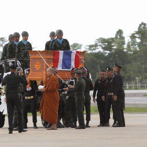 Buddhalainen munkki ja armeijan kunniavartiosto saattoivat kuolleen sukeltajan arkkua Chiang Rain lentokentällä.