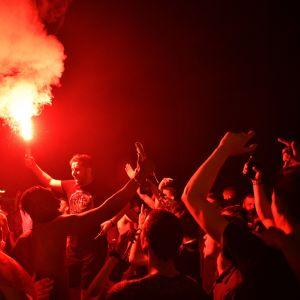 Joukko ihmisiä juhlii kädet kohotettuina, keskellä mies pitää punaista savusoihua ilmassa.