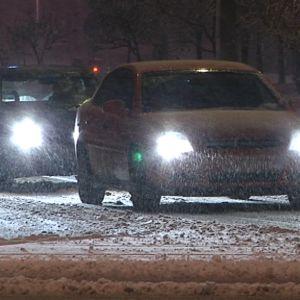 Kolme autoa ajaa hiljaa ajovalot loistaen hämärässä. Räntää sataa.